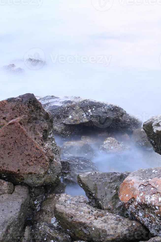 vågor och stenar lång exponering foto