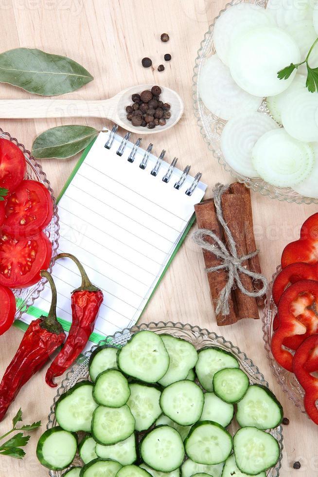 färska skivade grönsaker med kryddor och en anteckningsbok för recept. foto