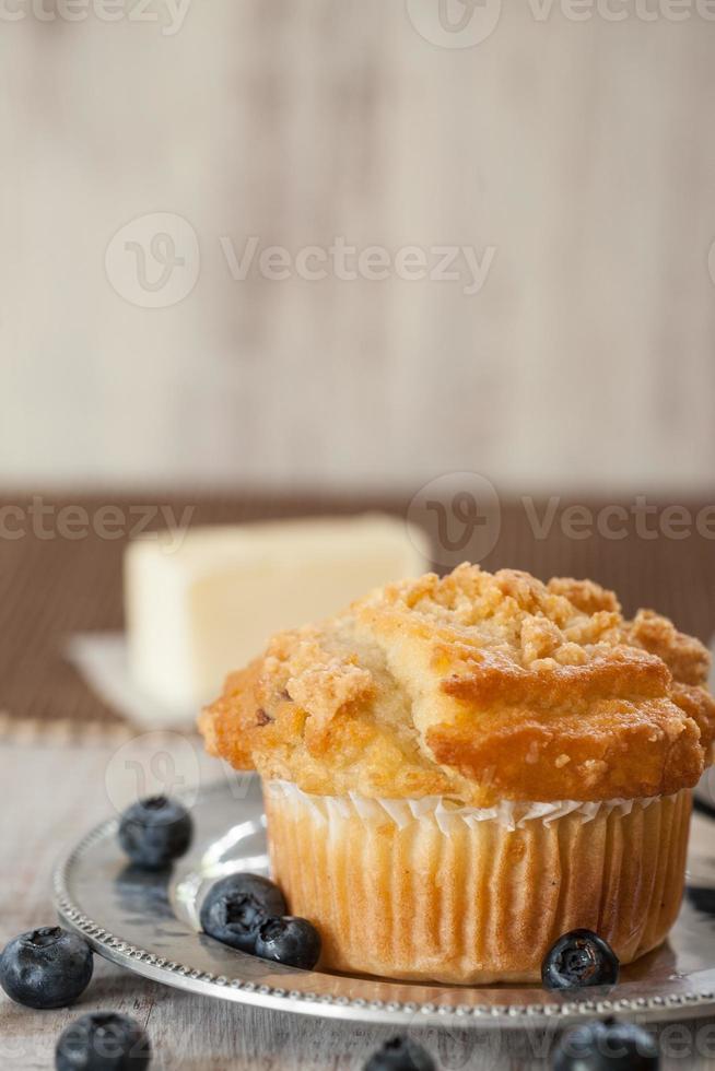 blåbärmuffin med blåbär och smör i bakgrunden foto