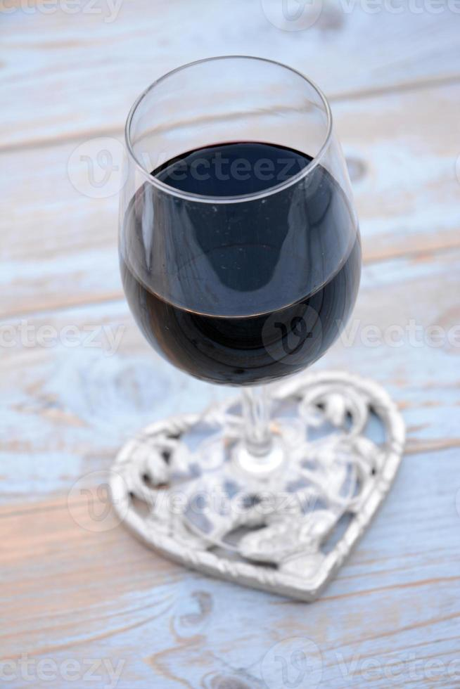 glas rött vin med ros- och hjärtdekoration foto