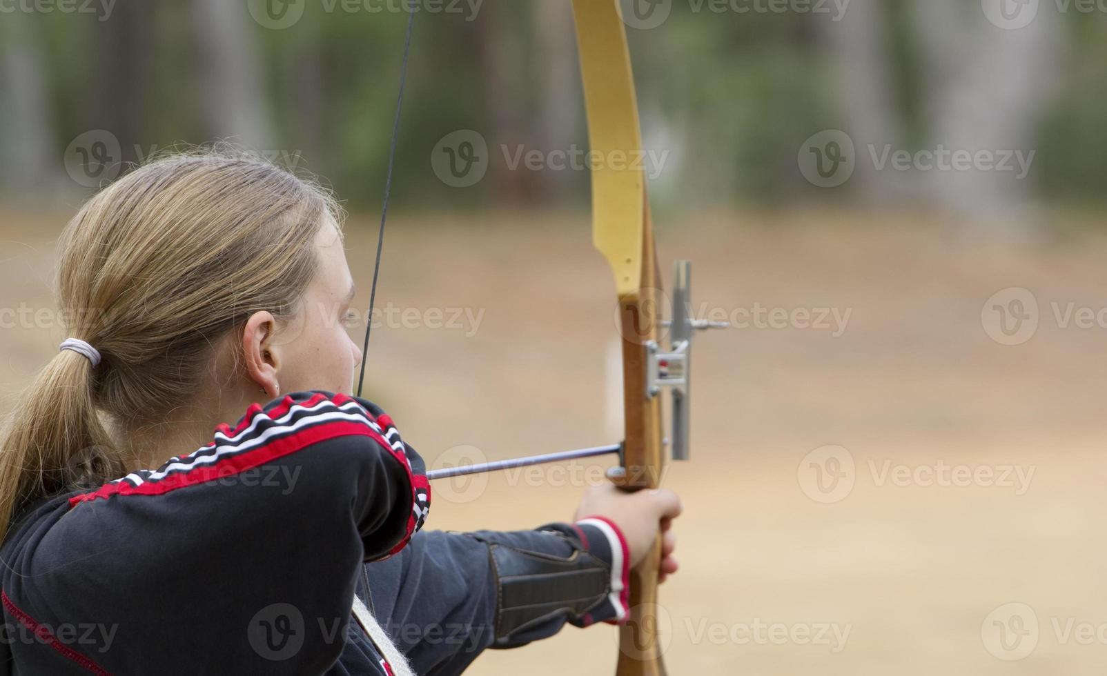 tonårsflicka som gör bågskytte foto