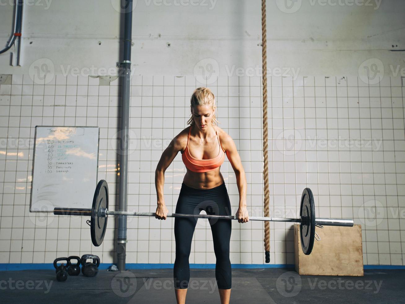 gym kvinna lyfta tunga vikter i gymmet foto
