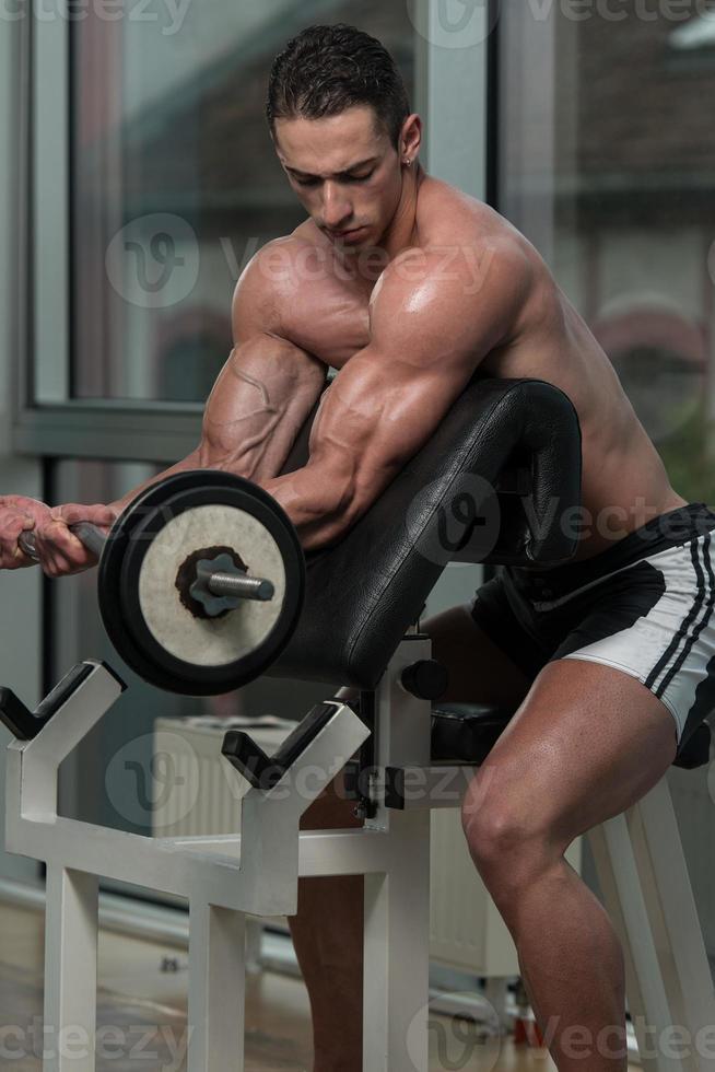 kroppsbyggare utför biceps lockar med en skivstång foto
