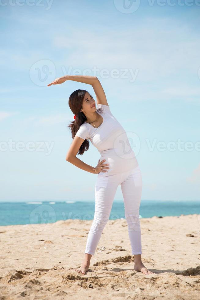 gravid asiatisk kvinna övning på stranden foto