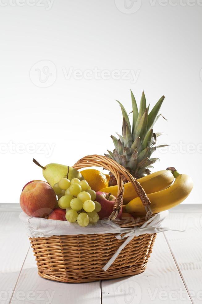 fruktkorg med ananas, bananer, citron, äpple, persikor, druvor foto
