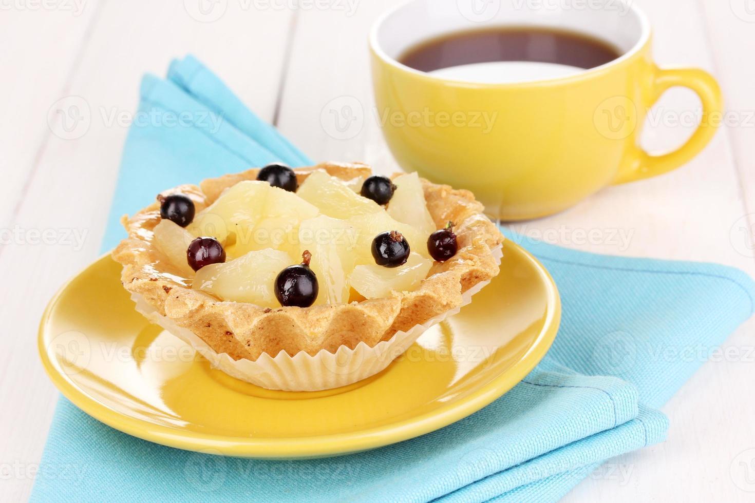 söt tårta med kopp te på träbakgrund foto