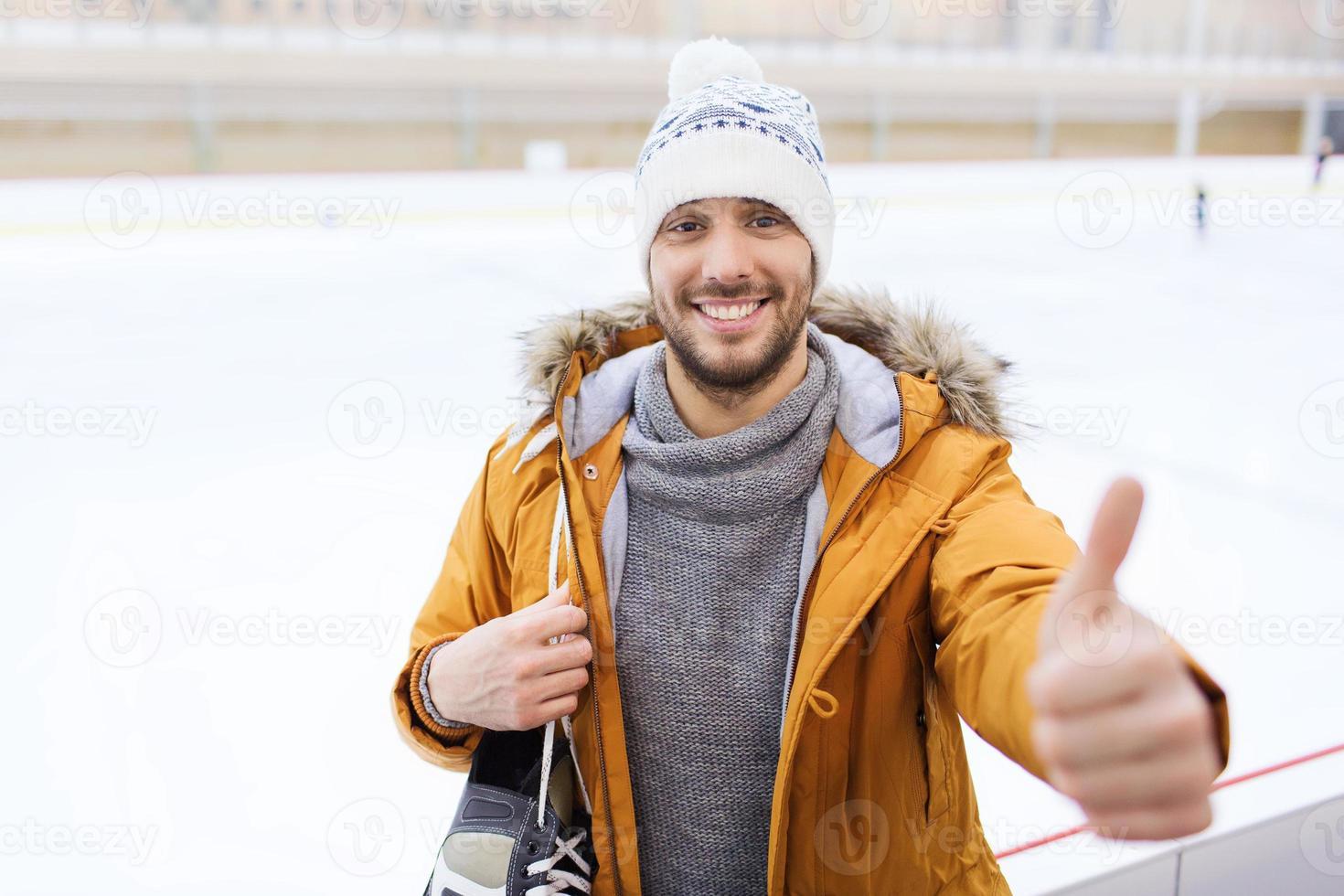 glad ung man visar tummen upp på skridskobanan foto