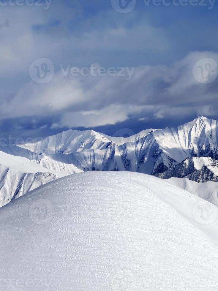 överst på snöiga sluttningen för pist och molniga berg foto