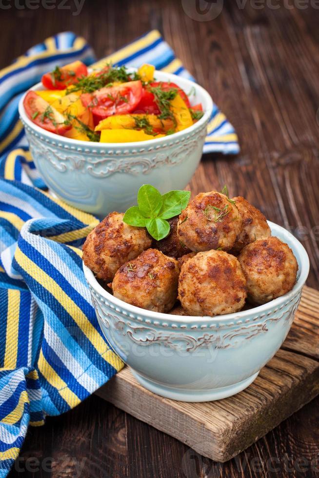 köttbullar i en skål och salladgrönsaker foto