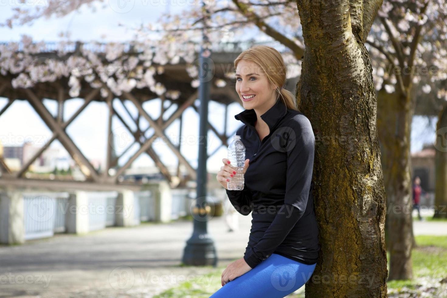 atletisk ung kvinna vilar mot träd foto