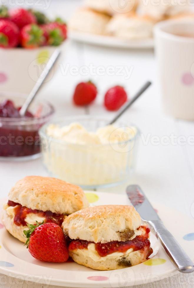 hembakade scones jordgubbssylt, koagulerade grädde jordgubbar och te. foto