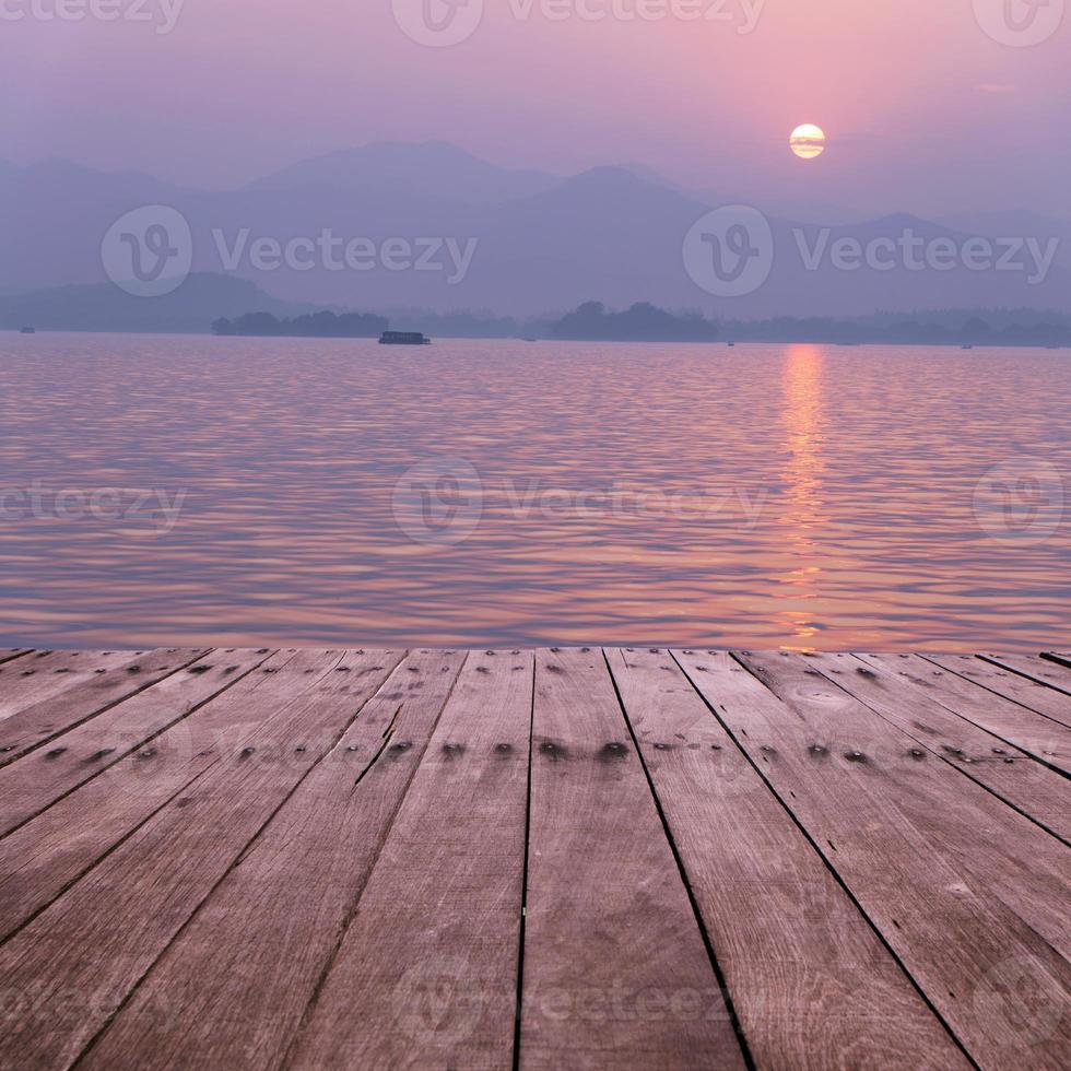 plankbräde med sjön i solnedgången som bakgrund foto