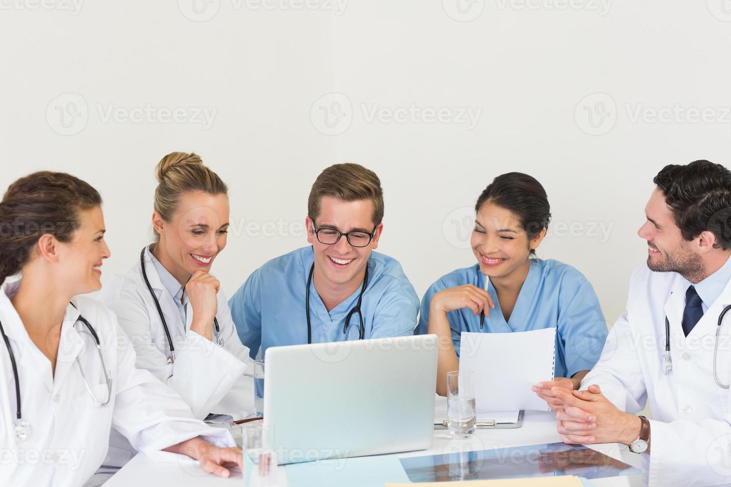 medicinskt team diskuterar över laptop foto
