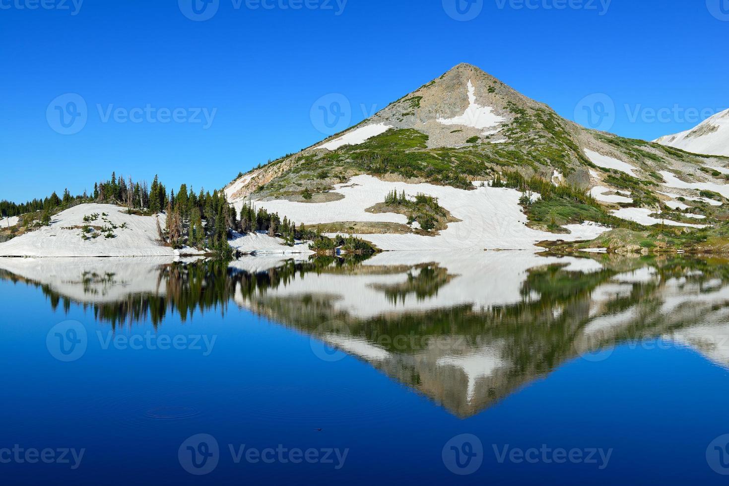 snöiga bergskedjor och alpin sjö med reflektion foto