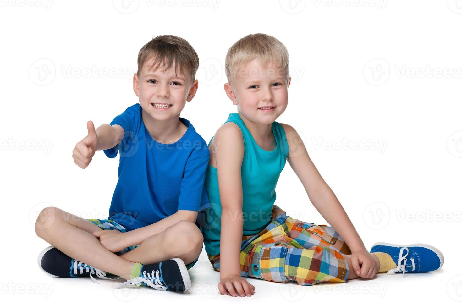 två små pojkar sitter tillsammans foto