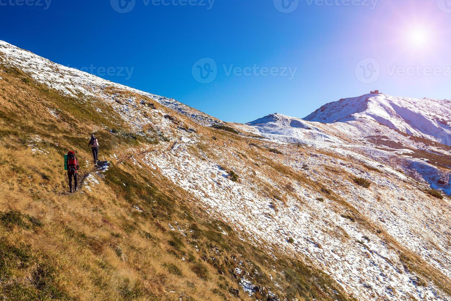 vinter bergskedja utsikt grupp vandrare gå upp på leden foto