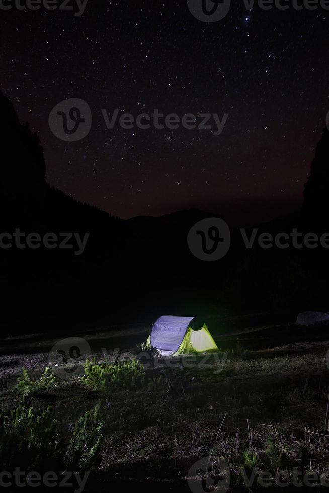 nattlandskap med tält uppfört på en bergsbetesmark foto