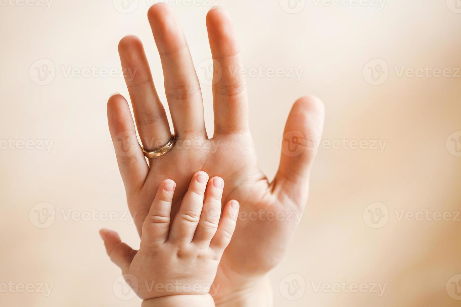 baby handflatan på hennes mammas handflata. foto