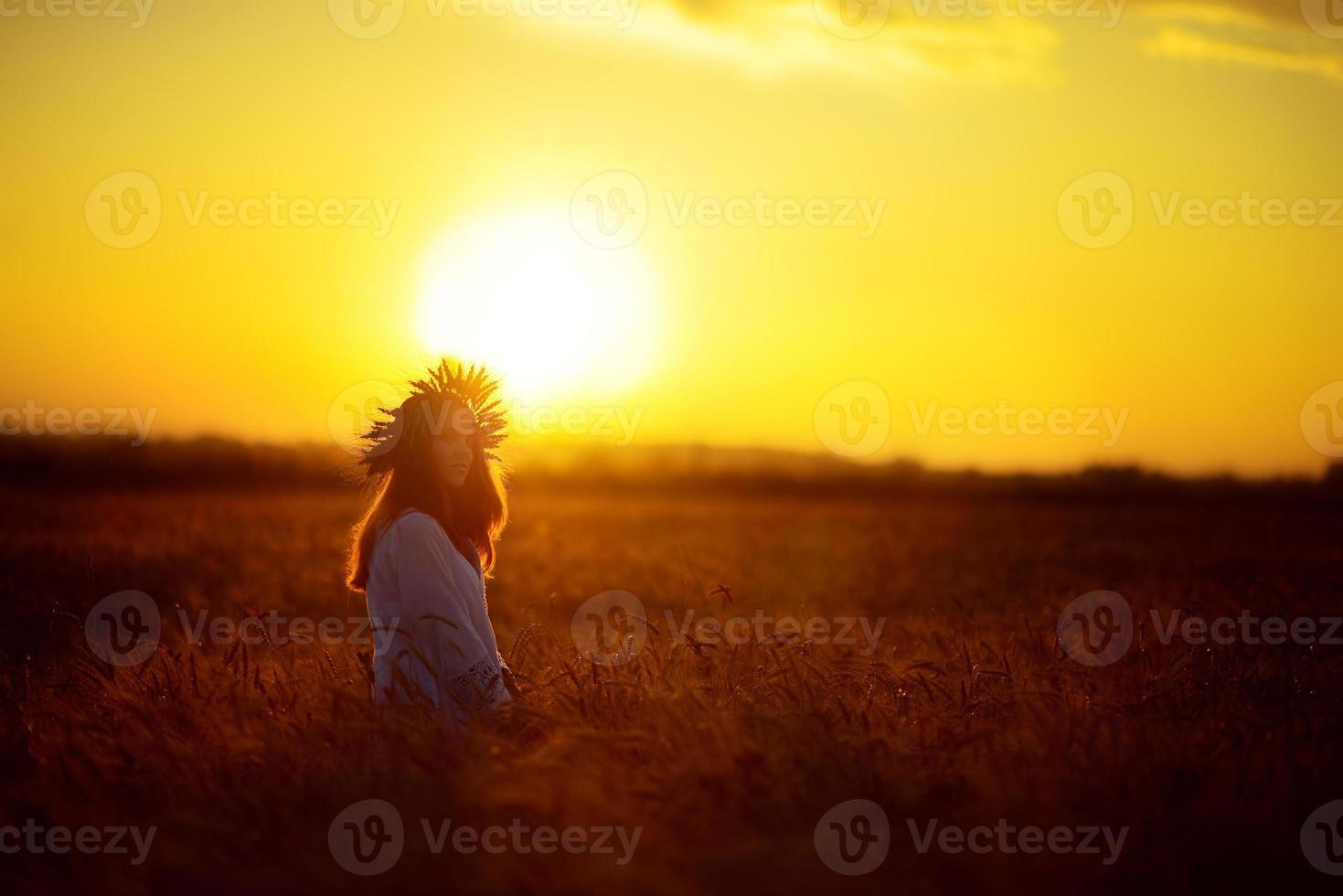 kvinna i ett vetefält vid solnedgången foto