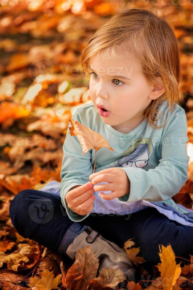 baby flicka på en höstbakgrund foto