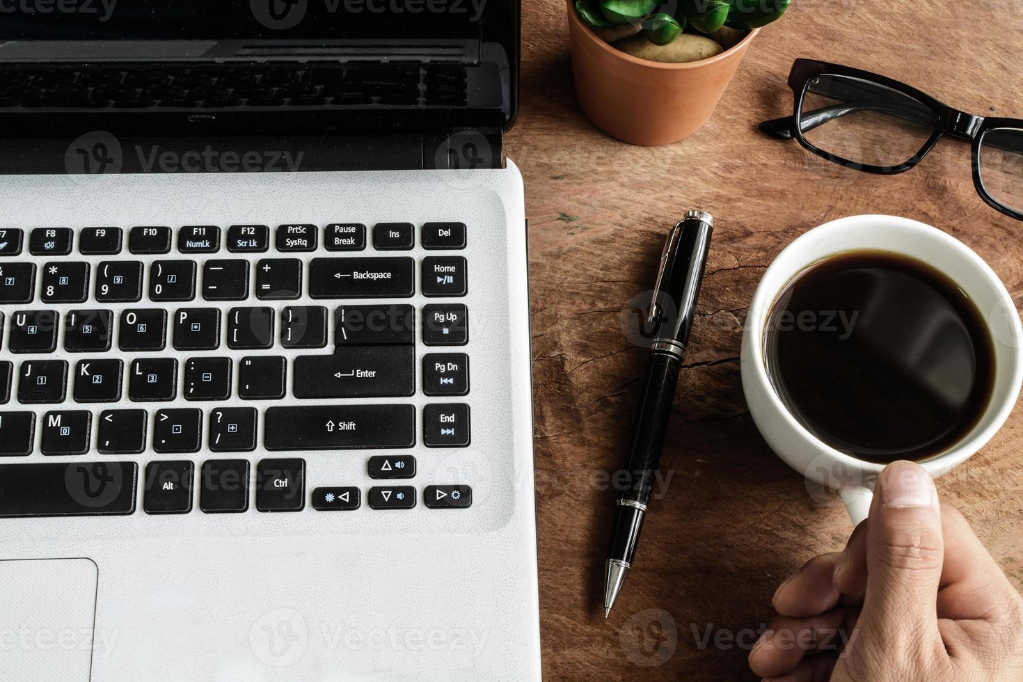 bärbar dator och kopp kaffe på gamla träbord foto