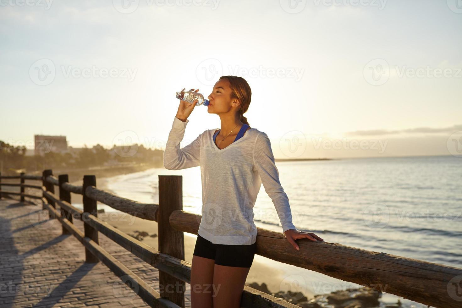 ung jogger som dricker en energidryck foto