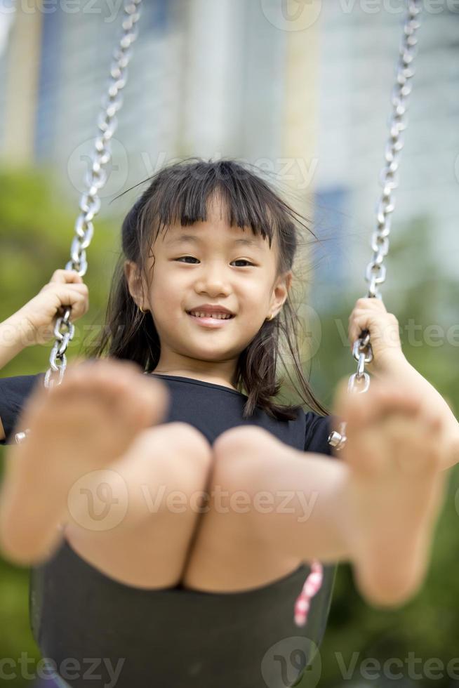 ung asiatisk tjej som spelar lyckligt i parken foto