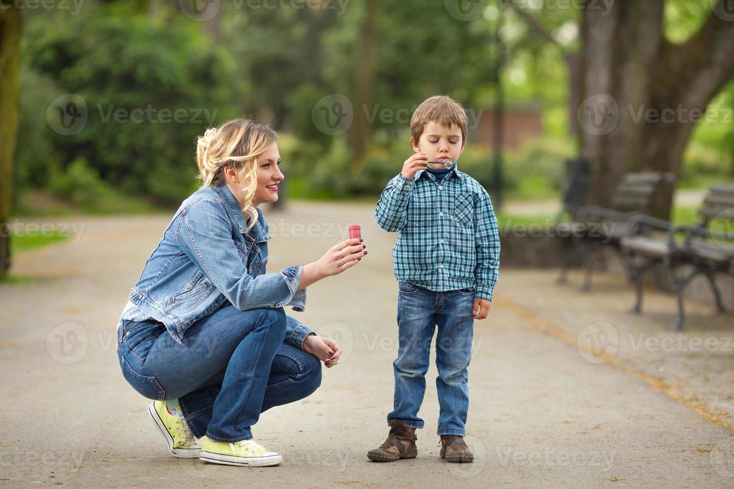 familjen blåser såpbubblor i en park foto
