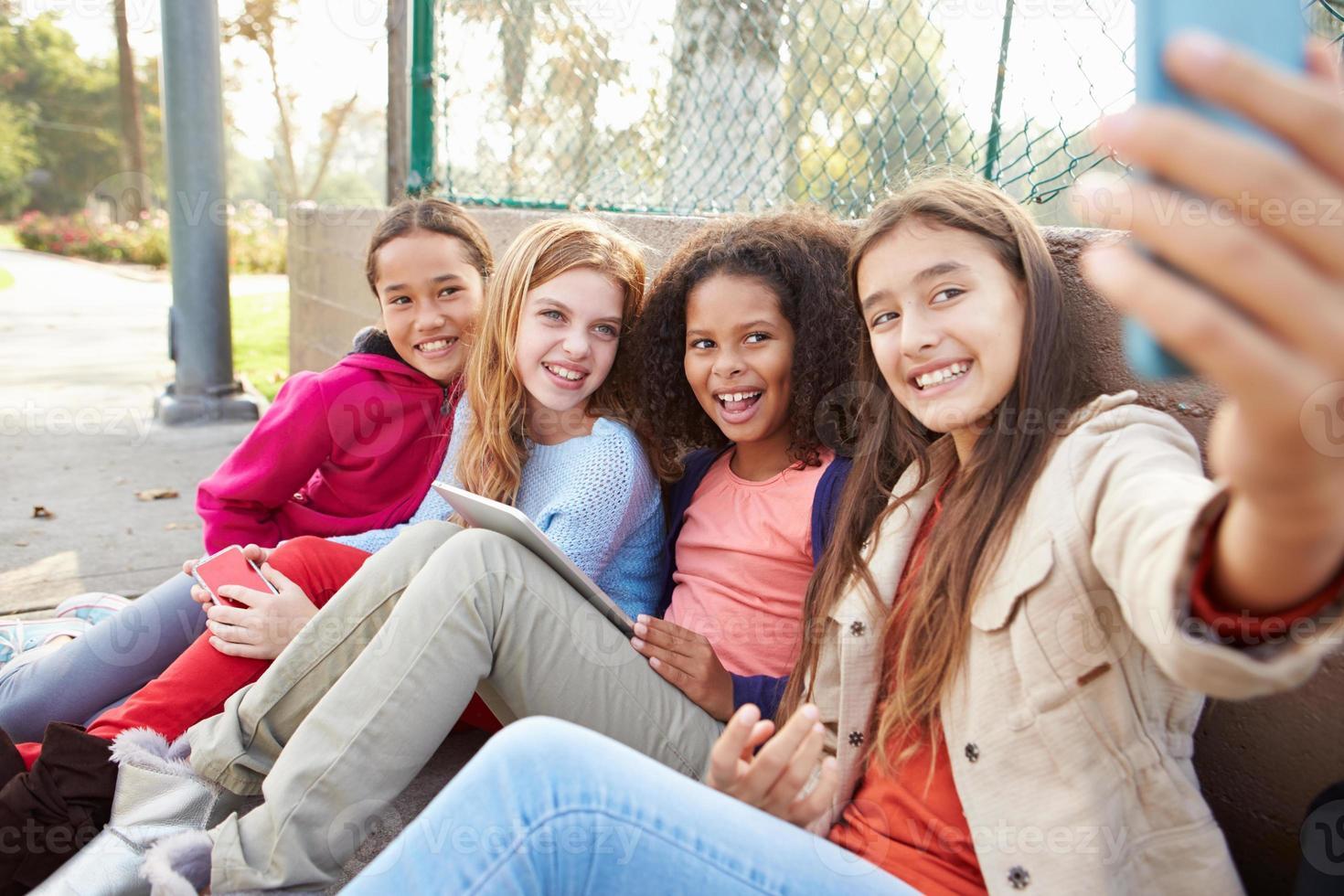 unga flickor tar selfie med mobiltelefonen i park foto