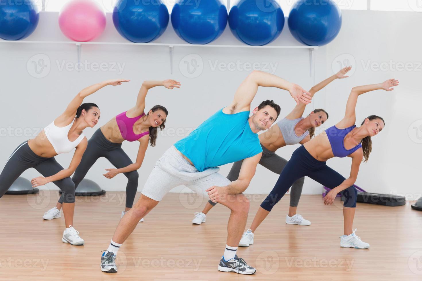 klass gör stretchingövning i fitnessstudio foto