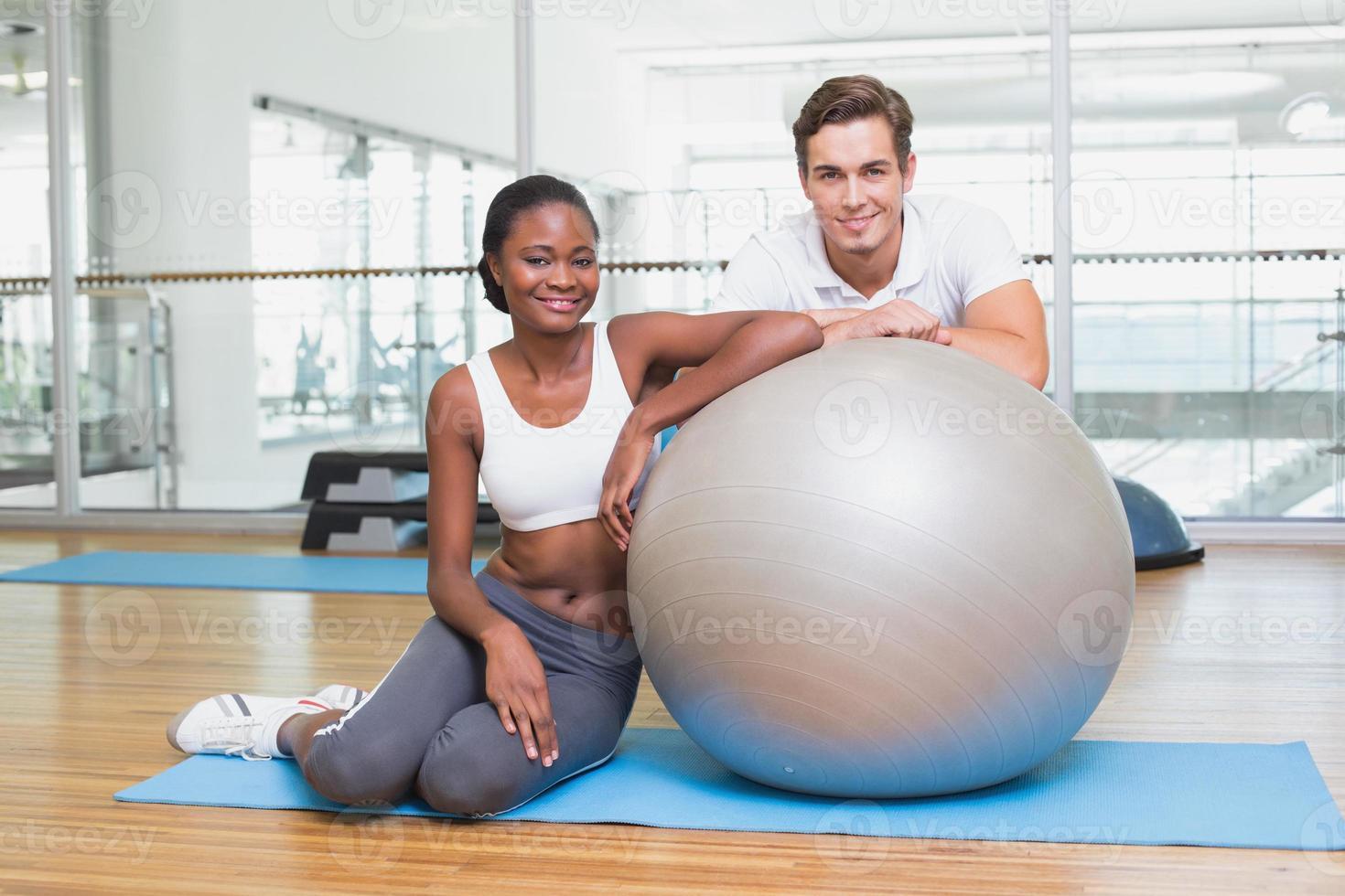 personlig tränare och klient som ler mot kameran med träningsboll foto