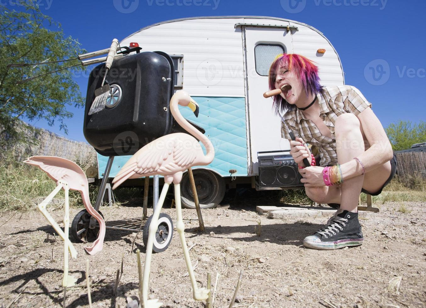 tjej framför trailern som äter en hotdog foto