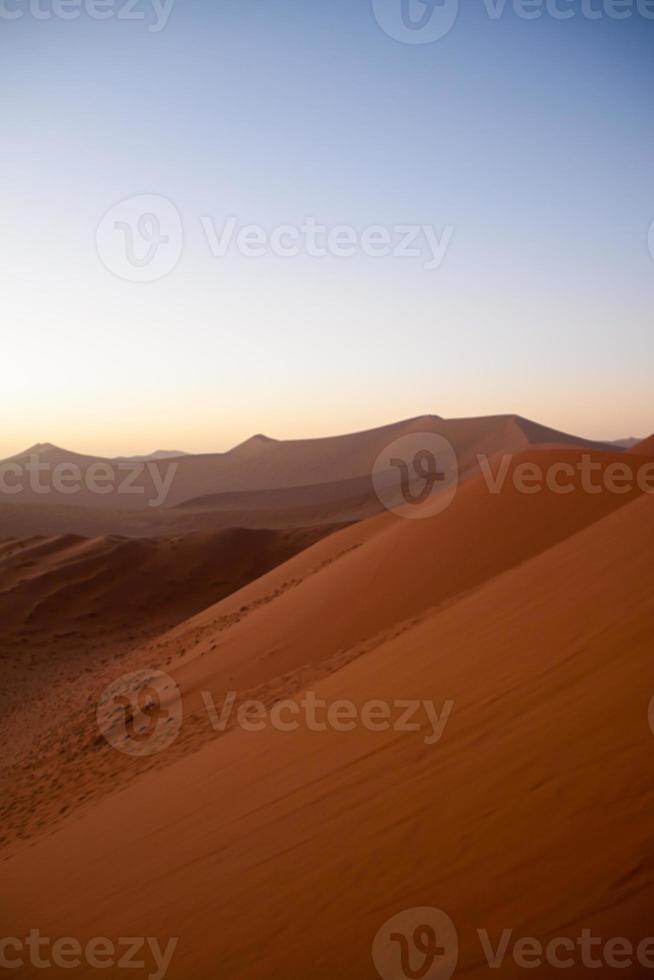soluppgång ovanför sanddyner i namib öknen, namibia foto