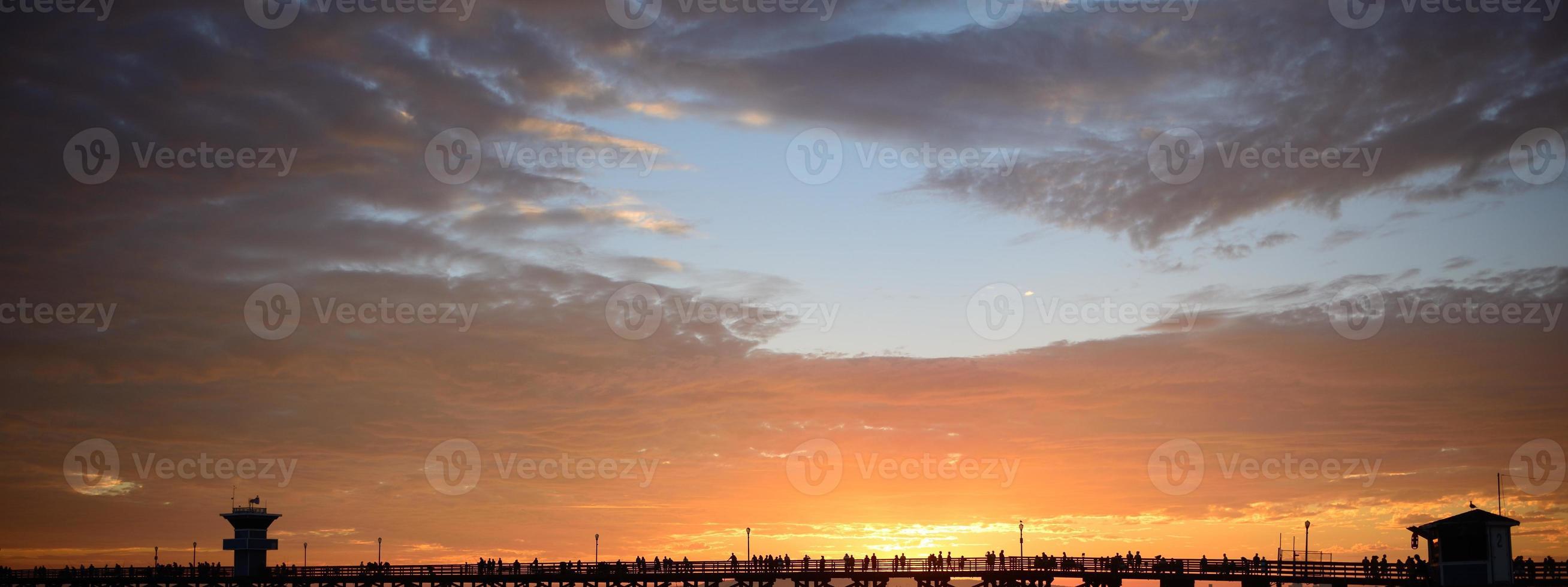 människor tittar på solnedgången från piren slutet av sommaren foto