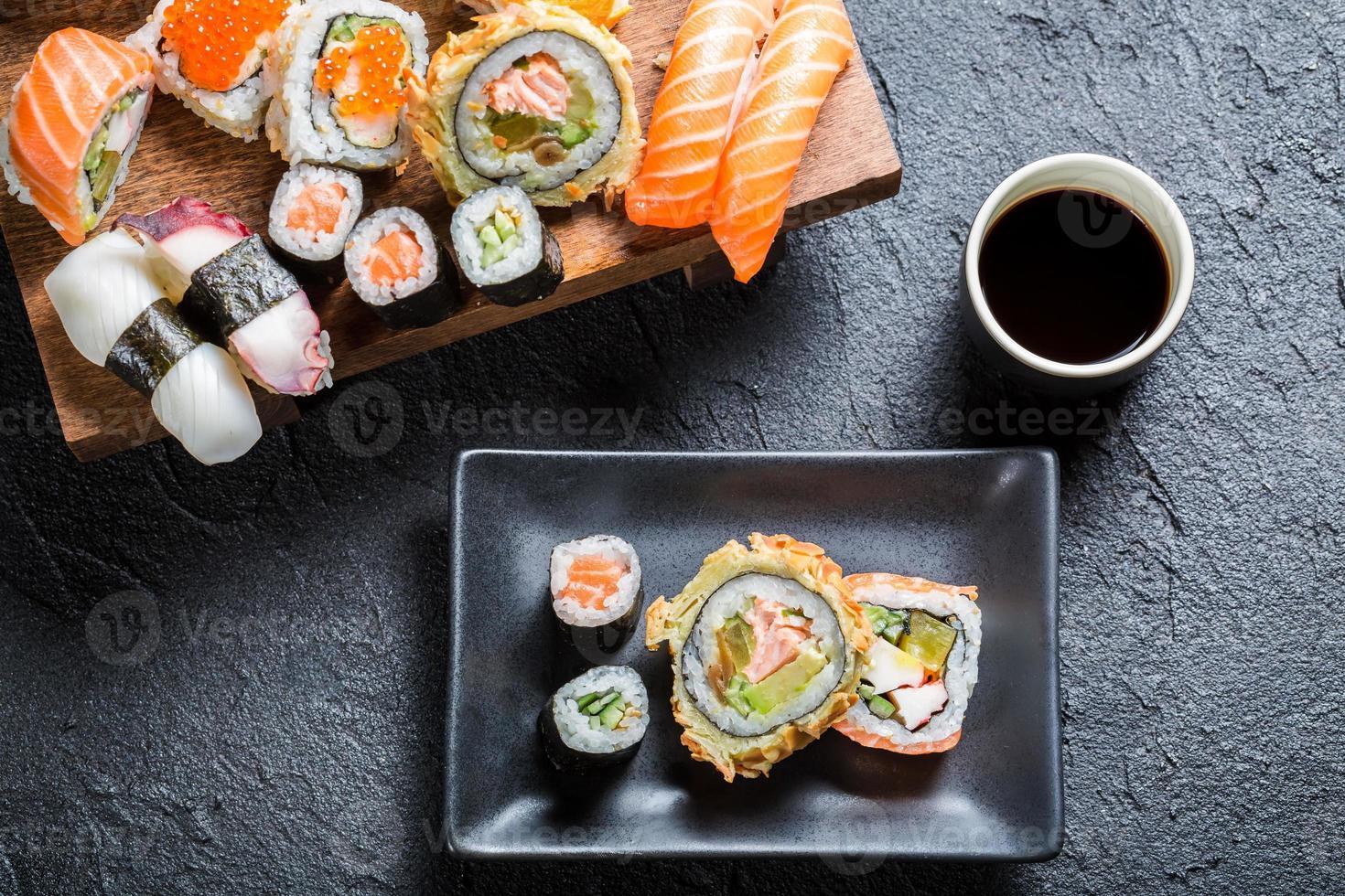 sushi serveras med sojasås på svart sten foto