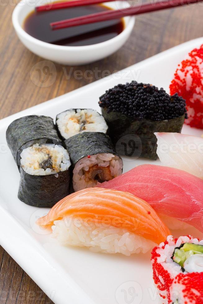 sushi uppsättning på en vit platta över vintage trä bakgrund foto