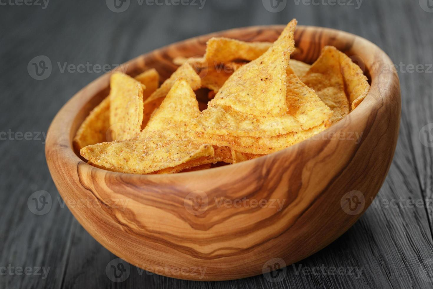 tortillachips i olivträskål på träbord foto