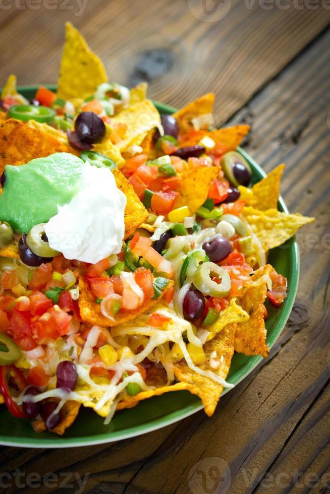 fullastade nachos i en grön platta på ett träbord foto