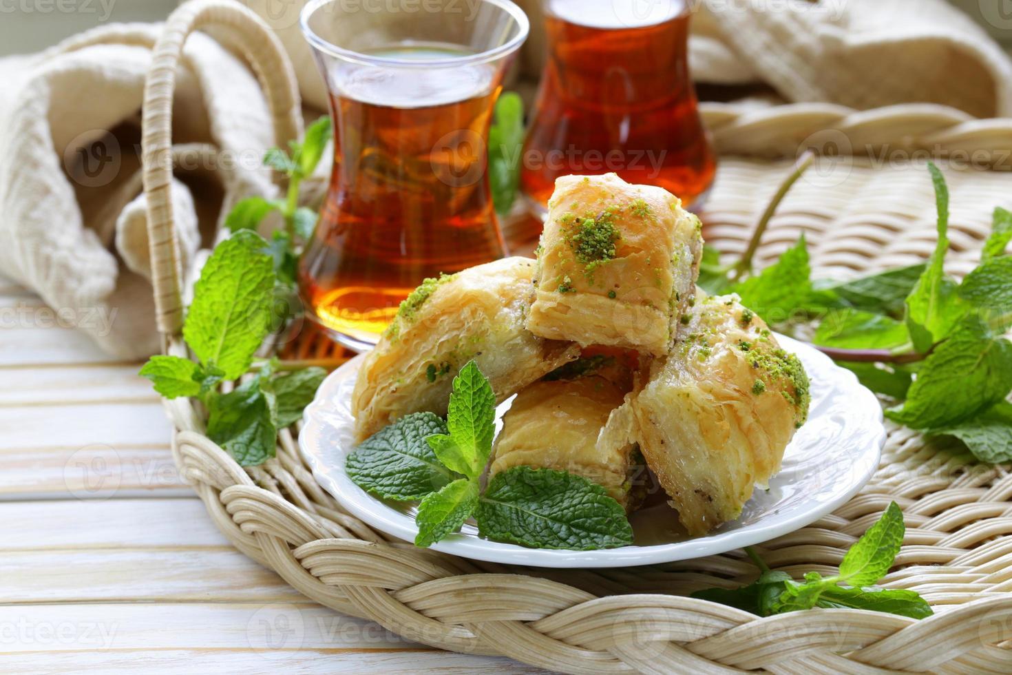 traditionell turkisk arabisk efterrätt - baklava med honung och pistascher foto