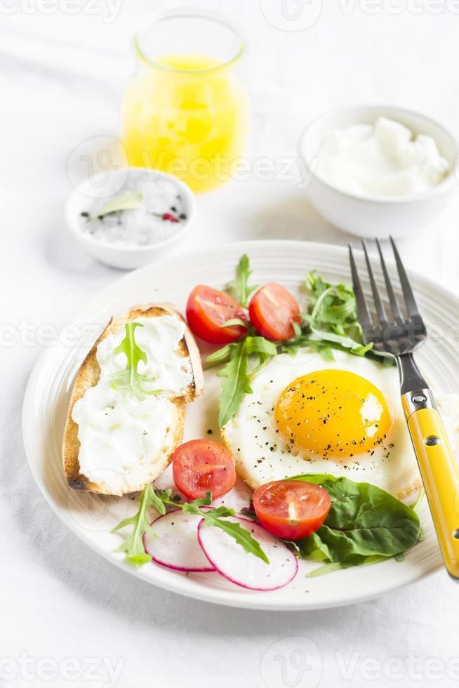 stekt ägg med tomater, ruccola, rädisor och rostat bröd med ost foto