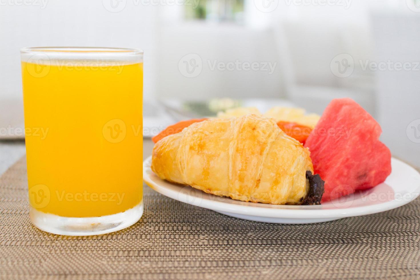 frukost med apelsinjuice, croissant och frukt foto
