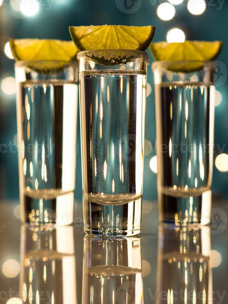 närbild av skottglas och limefrukter med bokehbakgrund foto