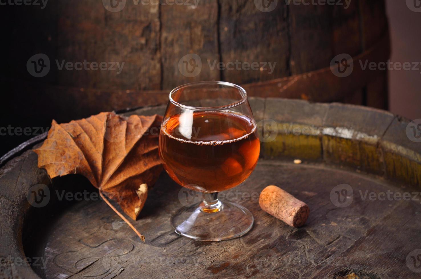 glas konjak på vintage träfat foto
