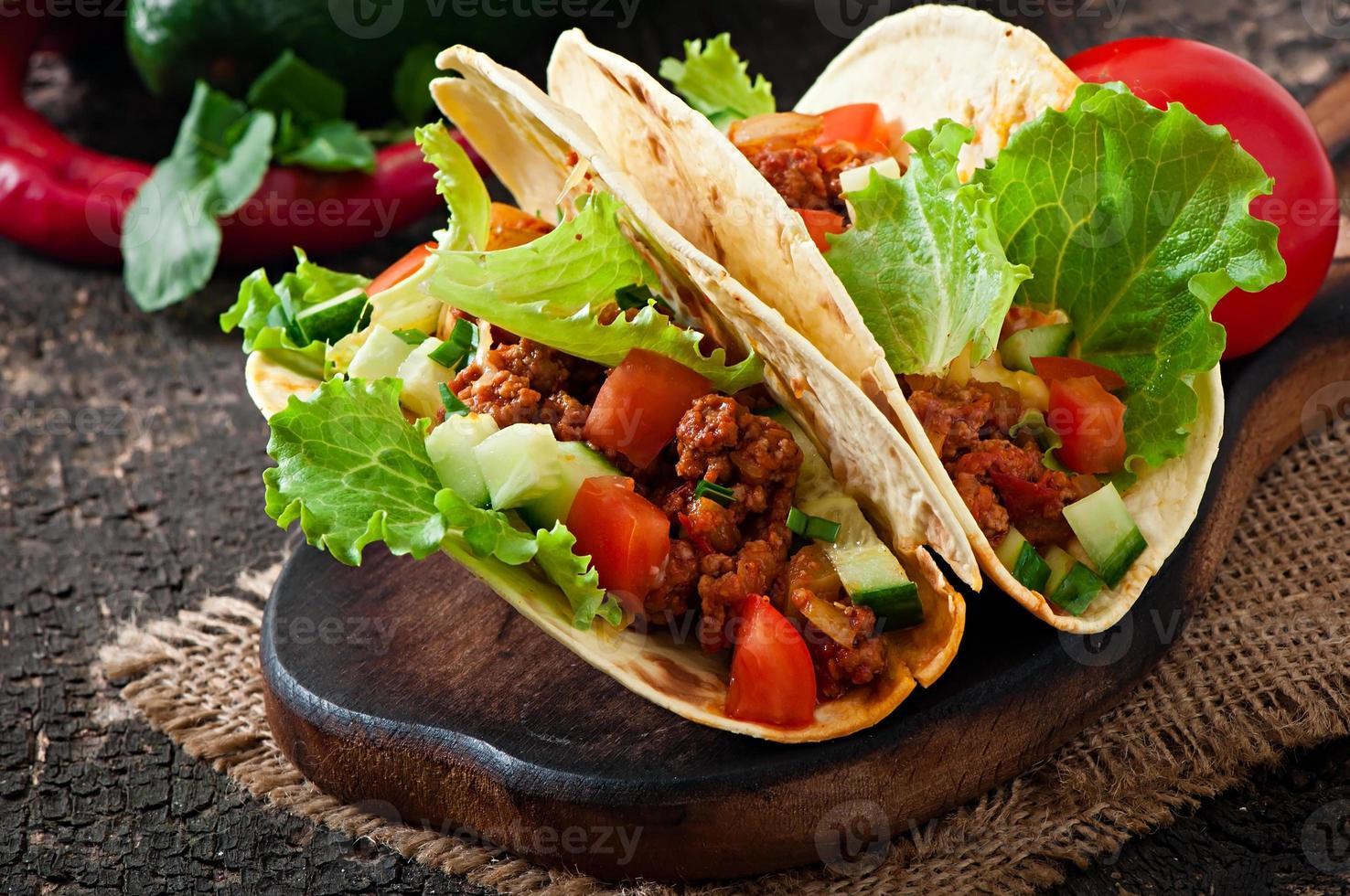 mexikanska tacos med kött, grönsaker och ost foto