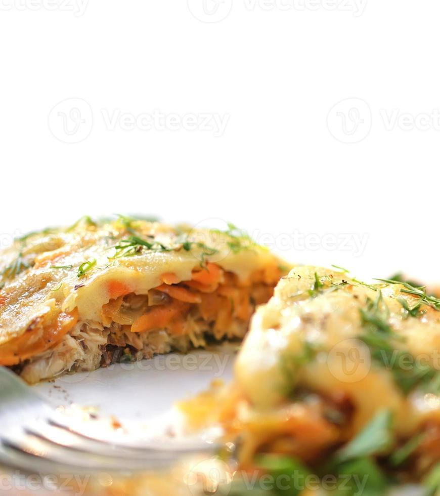 bakad fisk med ostsås, morötter och lök. foto