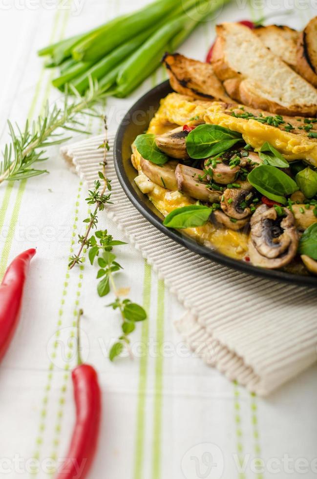 omelett med svamp, lammsallad, örter och chili foto