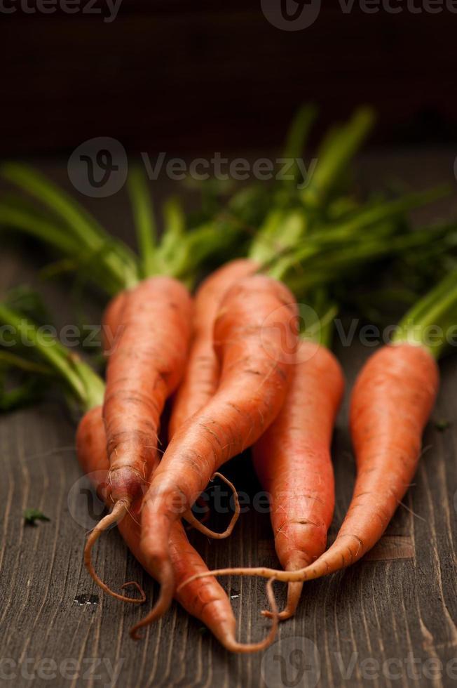rå morötter på träbord foto