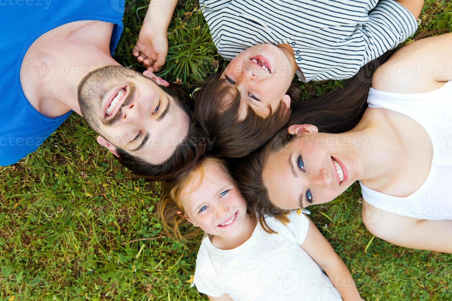 lycklig ung familj som ligger på gräset foto