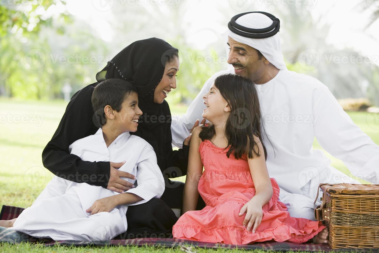 Mellanöstern familj sitter i en park foto
