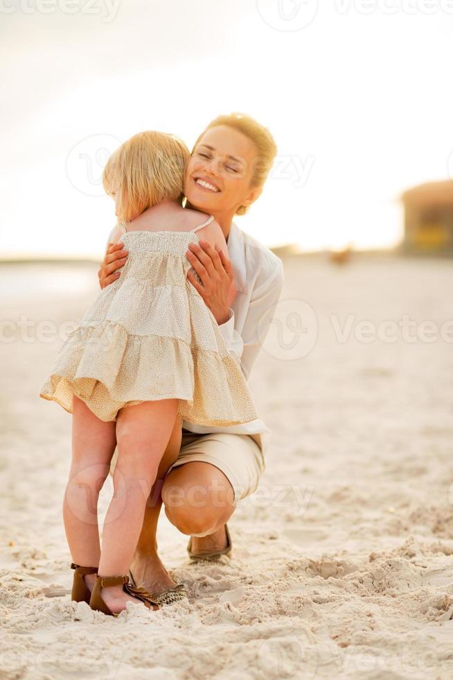 mamma och bebisflicka som kramar på stranden på kvällen foto